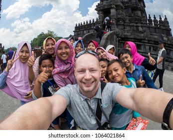 Yogyakarta, Indonesia - March 17, 2018: Caucasian man poses with local group of people at Prambanan temple in Yogyakarta