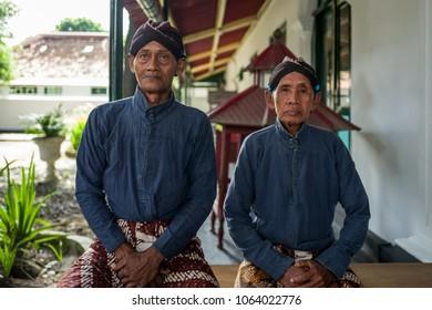 Yogyakarta, Indonesia - March 17, 2018: Two elderly man in tradional clothes at Kraton Palace in Yogyakarta