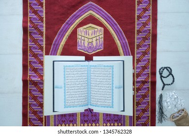 Yogyakarta, Indonesia - March 21, 2019: A Holy Qur'an on the top of prayer rugs. The Qur'an is the main book of Islamic religion. -Image