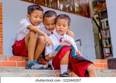 Yogyakarta, Indonesia - March 26th 2018 : Three children wearing school uniforms are learning together, Yogyakarta Indonesia