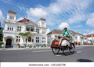 Yogyakarta, Indonesia - March 27th 2019 : Becak, traditional rikshaw transport on streets of Yogyakarta Java Indonesia.  A becak driver on his vehicle on a road in Yogyakarta looking out for clients