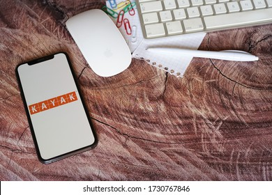 Yogyakarta, Indonesia - May 14, 2020; Kayak Iphone Screen on a Trunk Table with White Keyboard and Mouse. Kayak is an app for planning, booking and traveling. #Kayak