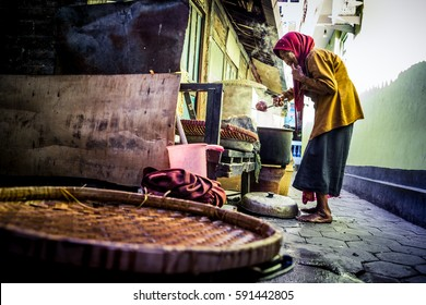 YOGYAKARTA, INDONESIA - OCT 9: Unidentified local woman boils potatoes in an alleyway in Yogyakarta on October 9, 2013.