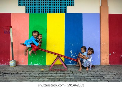 YOGYAKARTA, INDONESIA - OCT 9: Unidentified children play on a seesaw in fron of a colorful wall in Yogyakarta on October 9, 2013.
