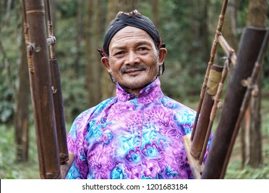 Yogyakarta, Indonesia. October, 13 2018. An old man dressed in Javanese customs plays a typical Indonesian musical instrument called angklung.