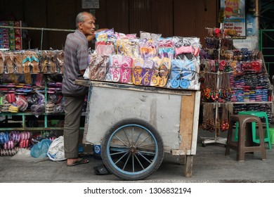 Yogyakarta, Indonesia - September 2018 :a street vendor in Malioboro waits for a buyer, sandals with Jogja's writing become typical souvenirs from Jogja.