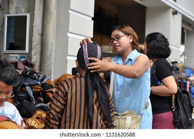 Yogyakarta, Indonesia-April 14, 2018:Domestic tourists are trying Blangkon in Jalan Malioboro Yogyakarta, Blangkon is a traditional hat from Central Java and Yogyakarta.