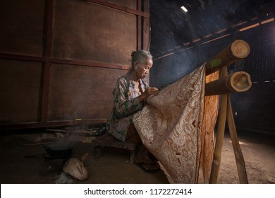 Yogyakarta, Indonesia-August 2016: An old lady is making batik at her old house in Yogyakarta. Batik is one of Indonesian heritages which has become an icon and national dress clothing in Indonesia.