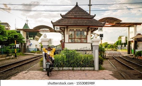 Yogyakarta, Java, Indonesia - February 4 2015: A man is relaxing on top of his motorbike at the crossing keeper station at the level crossing Mangkubumi Road