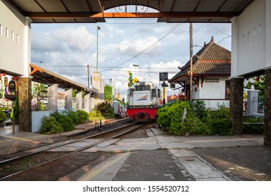 Yogyakarta, Java, Indonesia - February 4 2015: A train is passing by at the crossing keeper station at the level crossing Mangkubumi Road