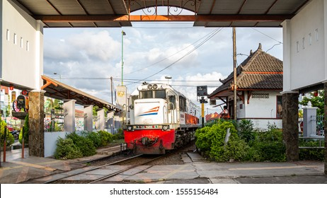 Yogyakarta, Java, Indonesia - February 4 2015: A A CC206 diesel locomotive is passing at the crossing keeper station and the station gate at the level crossing Mangkubumi Road