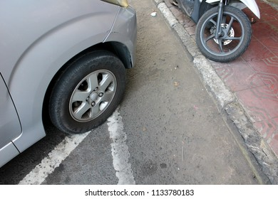 YOGYAKARTA JULY 2018 - Car is parking on the right row while scooter park illegally on the pedestrian ways so people can't walk safely during the day