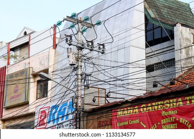 YOGYAKARTA JULY 2018 - Government developing a slum area with cross electricity cable in front of the commercial building