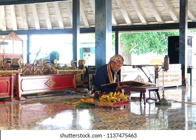 YOGYAKARTA JULY 2018 - An old abdi dalem or Sultan assistant is sitting on the floor while read an ancient Javanese script during morning performance inside the Sultan Palace