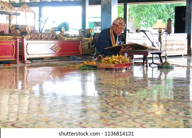YOGYAKARTA JULY 2018 - An old man is sitting on the floor and do poetry reading to all visitor of Sultan Palace during July holiday in Yogyakarta