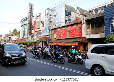 YOGYAKARTA JULY 2018 - Scooter and car are passing by crowded commercial area in Yogyakarta Indonesia during regular office hour