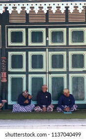 YOGYAKARTA JULY 2018 - Three men who belong to king's guard called abdi dalem are sitting together on a green carpet during visitor day in Sultan Palace park