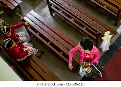 YOGYAKARTA MAY 2016 - Mom is talking to her sons while wearing traditional Javanese clothes called kebaya and surjan during wedding ceremonial in church