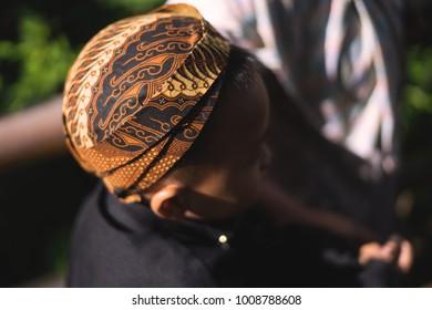 Yogyakarta,Indonesia - 22 January 2018 : Unidentified young Indonesian boy wearing traditional Java hat/blangkong was heading to the school at Yogyakarta.