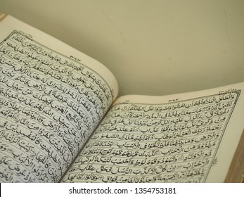 Yogyakarta/Indonesia - March 30 2019: Arabic text inside holy bible Al-Quran above Sajadah (prayer mat) during Islamic Ramadan 2019 exhibition