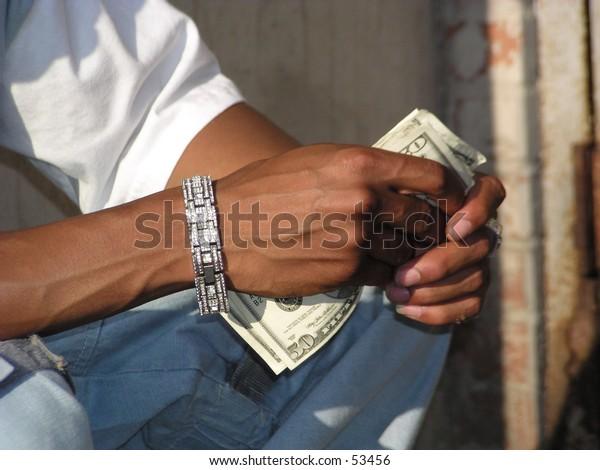 yoiung black man's hands with jewelery and plenty of money