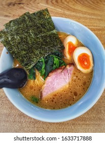 Yokohama Iekei ramen /Japanese shoyu - tonkotsu oily ramen / soy sauce - pork bone broth noodle with tasted half boiled egg, spinach, seaweed, and shashu / roasted pork - common daily Japanese food