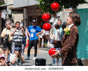 YOKOHAMA, JAPAN - APRIL 22, 2018: Street performer is juggling red balls on the street in the International Street Performers Festival on April 22 in Yokohama. People are looking at the acrobatics.