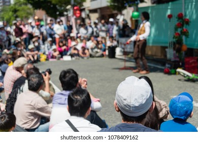 YOKOHAMA, JAPAN - APRIL 22, 2018: People are looking at acrobatics on the street in the International Street Performers Festival. A performer is balancing a ball on the stick held by the mouth.