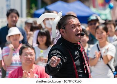 YOKOHAMA, JAPAN - APRIL 22, 2018: Street performer is singing songs on the  street in the International Street Performers Festival on April 22 in Yokohama, Japan. People are looking at the performer.