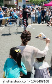 YOKOHAMA, JAPAN - APRIL 22, 2018: People are looking at a balloon artist on the street in the International Street Performers Festival on April 22 in 2018. The performer is making a balloon art.