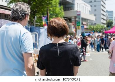 YOKOHAMA, JAPAN - APRIL 22, 2018: People are looking at a balloon artist on the street in the International Street Performers Festival on April 22 in Yokohama. The performer is making a balloon art.