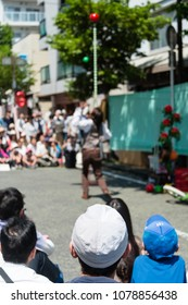 YOKOHAMA, JAPAN - APRIL 22, 2018: People are looking at acrobatics on the street in the International Street Performers Festival on April 22 in Yokohama. A performer is balancing a stick on the jaw.