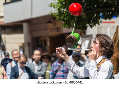 YOKOHAMA, JAPAN - APRIL 22, 2018: Street performer is balancing  a kettle and a ball on the stick in the International Street Performers Festival on April 22 in Yokohama. People are looking at him.