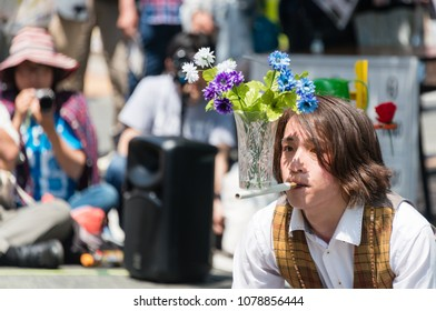YOKOHAMA, JAPAN - APRIL 22, 2018: Street performer is balancing a flower vase on the stick in the International Street Performers Festival on April 22, 2018 in Yokohama. People are looking at him.