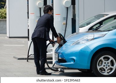 YOKOHAMA, JAPAN - APRIL 24, 2014: A businessman plugs in an electric car Nissan Leaf to charge the car at a charging station in front of the entrance of Nissan's Global Headquarters.