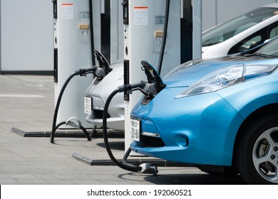 "YOKOHAMA, JAPAN - APRIL 24, 2014: Electric cars, Nissan's ""Leaf"", are being charged at the charging stations in front of the entrance of Nissan's global Headquarters located in Yokohama, Japan."