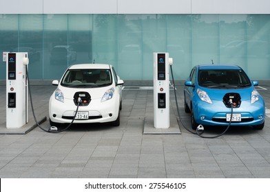 """YOKOHAMA, JAPAN - APRIL 25, 2015: Electric cars, Nissan's """"Leaf"""", are being charged at the charging stations in front of the entrance of Nissan's Global Headquarters located in Yokohama, Japan."""