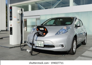 """YOKOHAMA, JAPAN - DECEMBER 1st, 2013: Nissan's electric car, called """"Nissan leaf"""", is being charged at the charging station in front of the entrance of the Nissan Global Headquarters."""