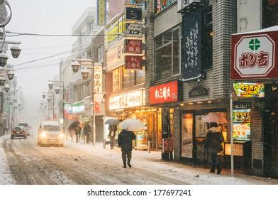 Yokohama, Japan - February 8, 2014: Japanese people walks across the street in snow storm in Yokohama, Japan