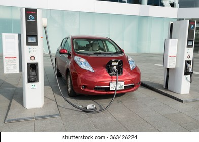 """YOKOHAMA, JAPAN - JANUARY 15, 2016: A NIssan's electric car """"Nissan Leaf"""" is being charged at the charging station in front of the entrance of Nissan's global headquarters located in Yokohama, Japan."""