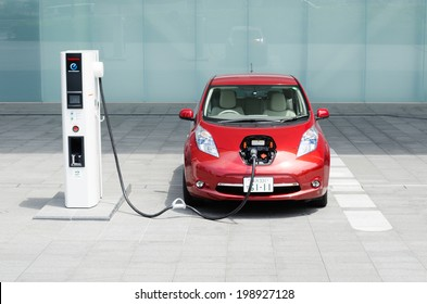 """YOKOHAMA, JAPAN - JUNE 14, 2012: A NIssan's electric car """"Nissan Leaf"""" is being charged at the charging station of Nissan's global headquarters located in Yokohama, Japan."""