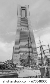 YOKOHAMA, JAPAN - MAY 3, 2017: The famous sailing ship the Nippon Maru is moored in front of the Yokohama Landmark Tower in this dramatic monochrome image.
