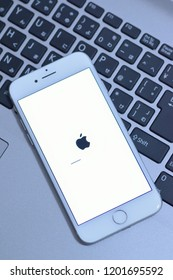 YOKOHAMA, JAPAN - October 12, 2018 : iPhone during iOS update with blurred laptop PC keyboard background. iPhone is industry leader cellphone brand & people wait for new features in iOS update