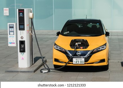 YOKOHAMA, JAPAN - OCTOBER 22, 2018: An electric car Nissan Leaf is being charged at the charging station in front of the entrance of Nissan's global headquarters which is located in Yokohama, Japan.