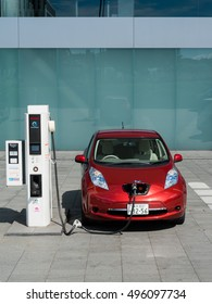 YOKOHAMA, JAPAN - SEPTEMBER 28, 2016: An electric car  Nissan Leaf is being charged at the charging station in front of the entrance of Nissan global headquarters which is located in Yokohama, Japan.