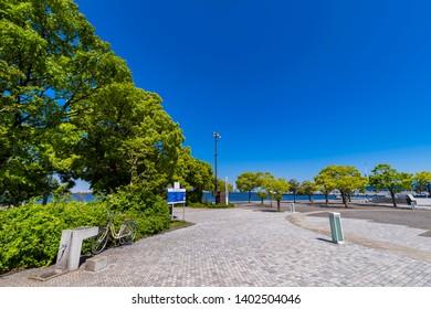 "YOKOHAMA, KANAGAWA / JAPAN - MAY 8 2019 : Landscape of ""Rinko Park"" in Yokohama. In the park facing the sea, you can see the Minato Mirai Building and Yokohama Bay Bridge."