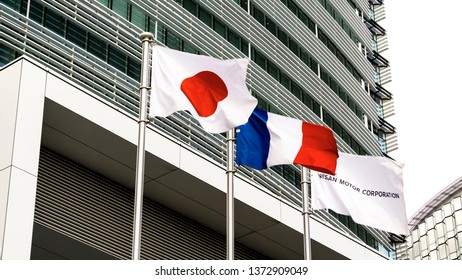 YOKOHAMA, KANAGAWA PREFECTURE, JAPAN - APRIL 15, 2019: Hoisted flags of Japan, France and Nissan Motor Corporation in front of Nissan Global Headquarters in Yokohama.