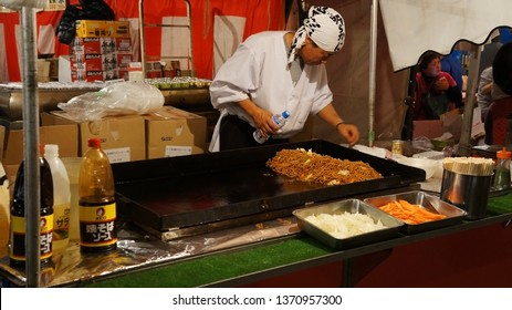 YOKOHAMA, KANAGAWA PREFECTURE, JAPAN - NOVEMBER 10, 2014: Man preparing yakisoba (Japanese stir-fry noodles) in a yatai food stall during Tori-no-Ichi annual festival at Kotohira-otori shrine.