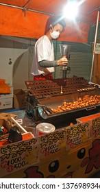 YOKOHAMA, KANAGAWA PREFECTURE, JAPAN - NOVEMBER 10, 2014: Man preparing Pikachu-shaped castella cakes in a yatai food stall, at Kotohira-otori shrine, during the annual Tori-no-Ichi festival.