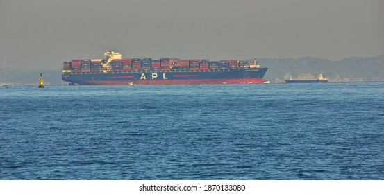 """YOKOSUKA CITY, KANAGAWA PREFECTURE, JAPAN - DECEMBER 7th, 2020: """"President Eisenhower,"""" a Huge Container Ship, Sailing through the Uraga Channel in Tokyo Bay toward the Pacific on a Sunny but Hazy Day"""